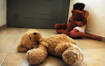 Abused child sitting on the floor in her home hold her teddy bear, suffering from a severe depression.